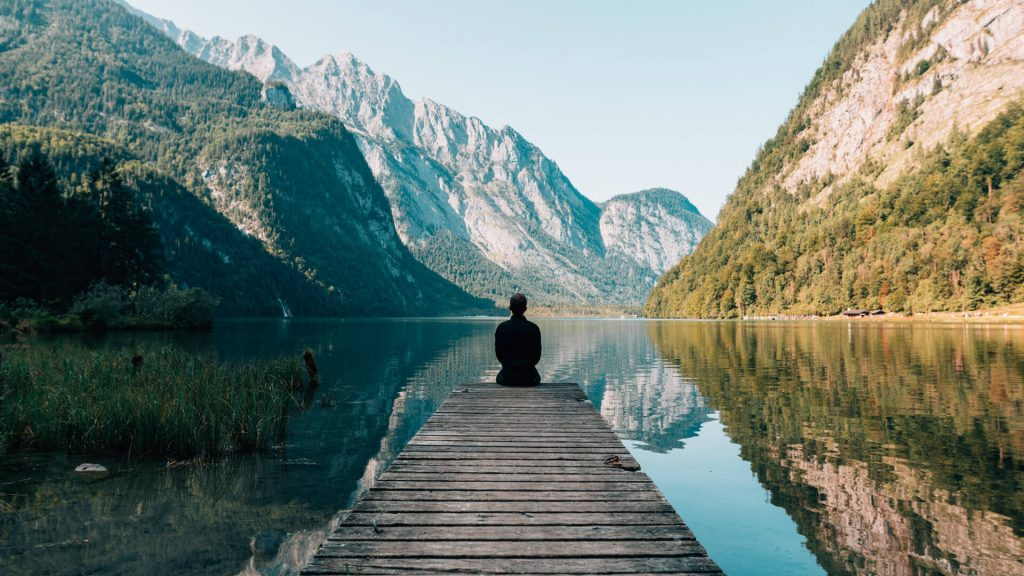 Man sitting by lake with beautiful mountain view